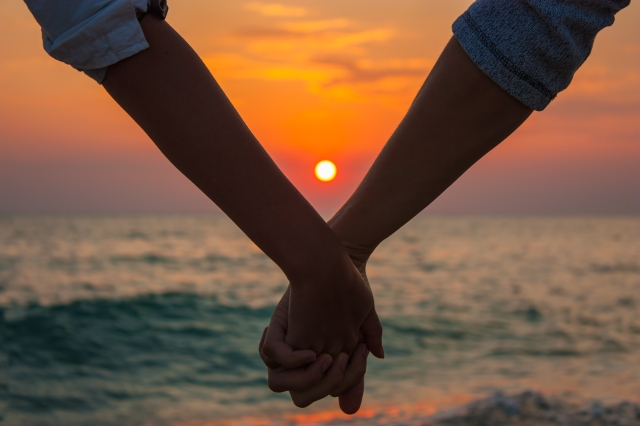 Couple Holding Hands at Sea Sunset